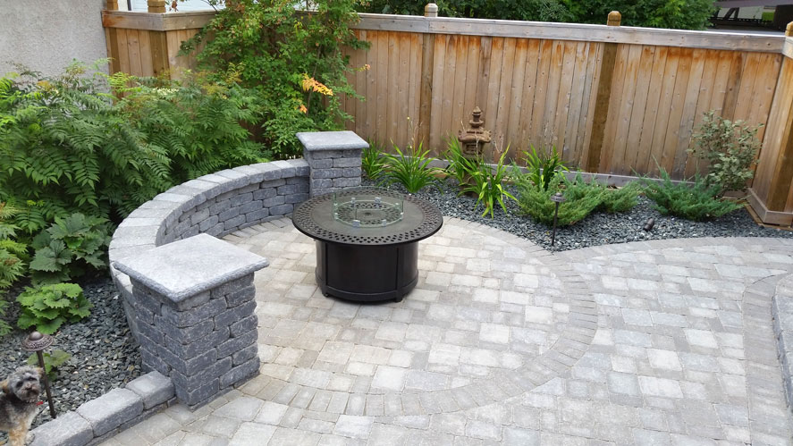 Inspired backyard brick-work with propane fire pit on Brock Street
