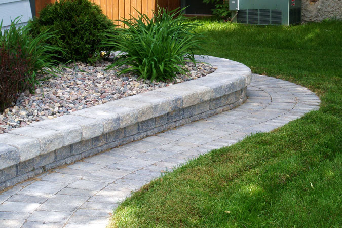 Stone retaining wall and pathway around shrubs on Aspen Cove